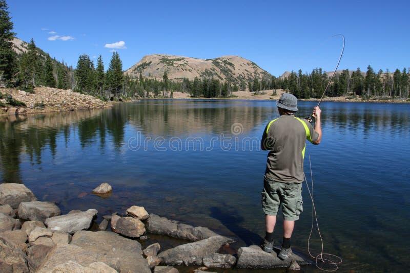 Pesca de mosca del hombre en el lago foto de archivo