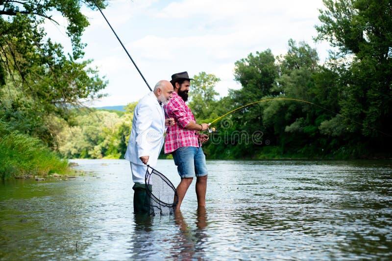 Pesca de mosca en el desierto prístino de Rusia Angler Padre e hijo felices pescando en el río con barras de pesca imágenes de archivo libres de regalías