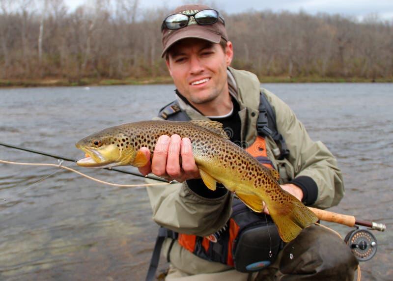 Pesca de mosca - peixe da terra arrendada do pescador (foco dos peixes) foto de stock royalty free