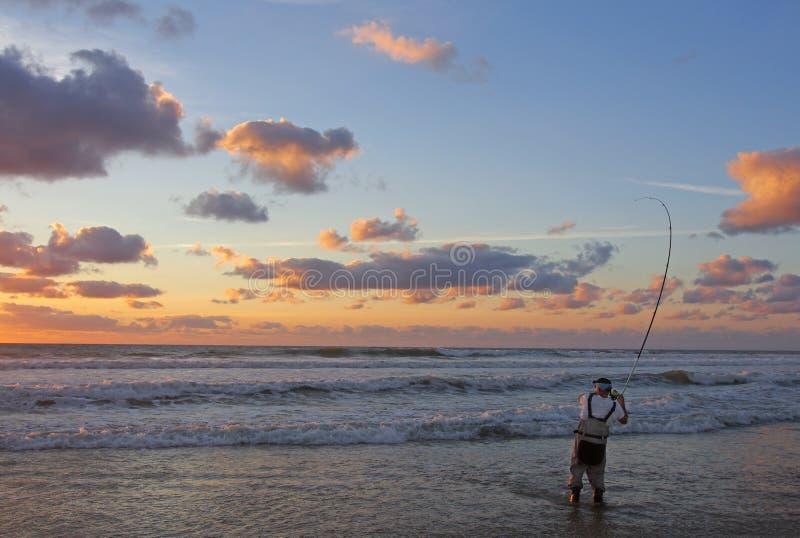 Pesca de resaca en la puesta del sol fotos de archivo
