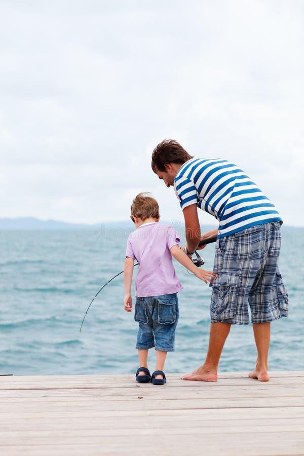 Pesca del figlio e del padre dal molo fotografia stock