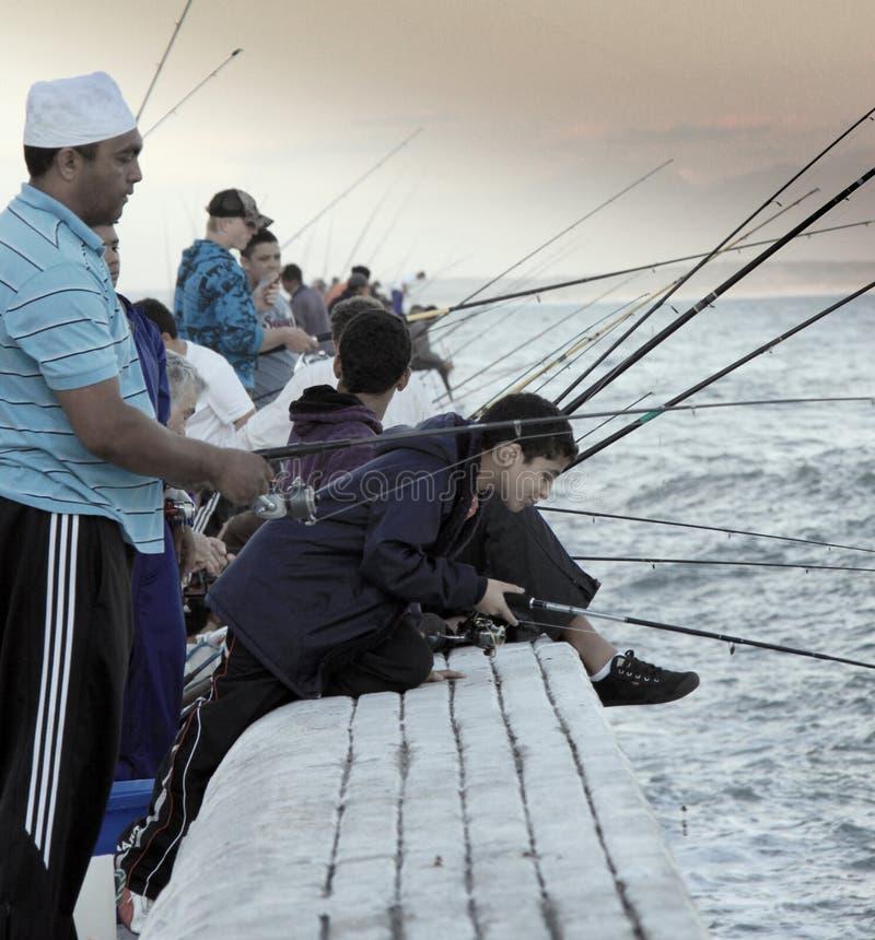 Pesca del grupo de personas en las aguas falsas de la bahía imagenes de archivo