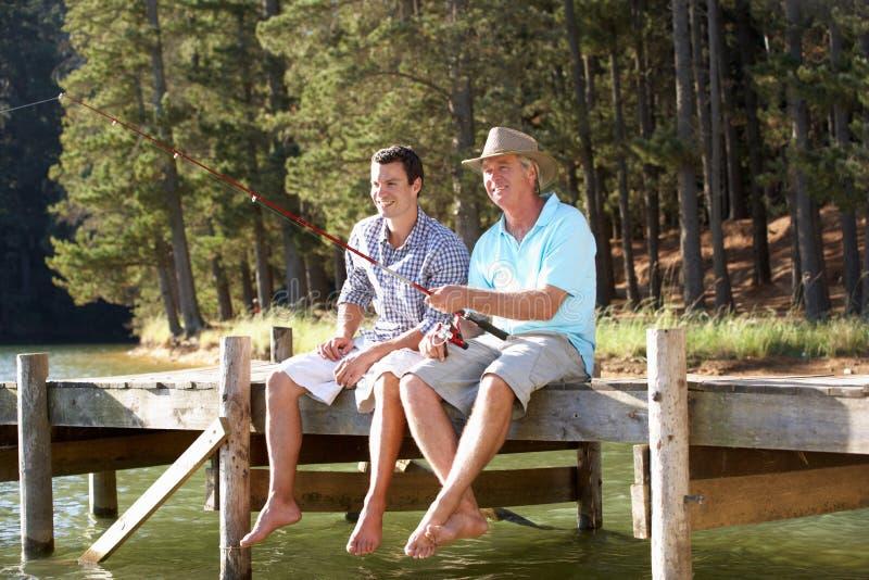 Pesca del hijo del padre y del adulto en el lago fotos de archivo