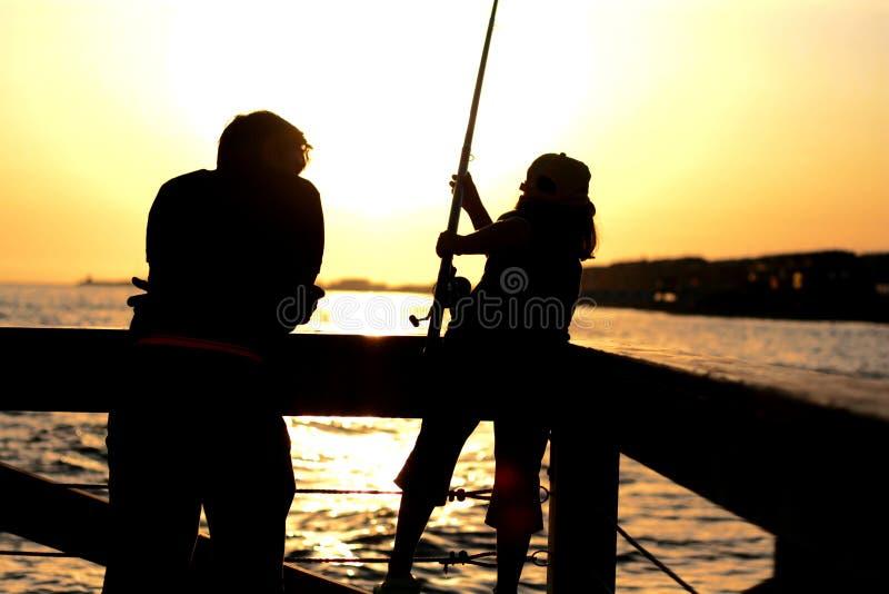 Pesca del hijo del papá n en el amanecer imagenes de archivo
