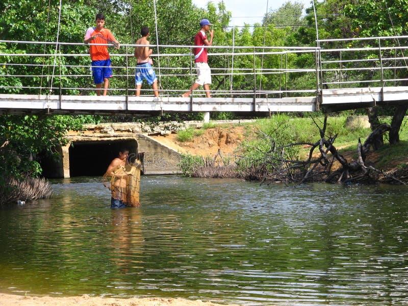 Pesca del hombre en el dren de Laguna de los Patos, Cumana, Venezuela fotografía de archivo