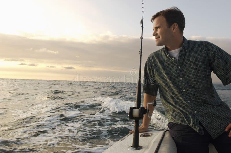 Pesca del hombre en el yate imagen de archivo libre de regalías
