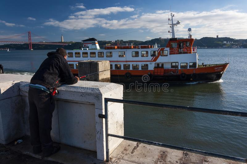 Pesca del hombre en la orilla del río Tagus con un barco del cacilheiro en el fondo, en la ciudad de Lisboa imagen de archivo