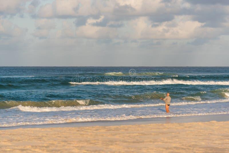 Pesca del hombre en la playa foto de archivo libre de regalías