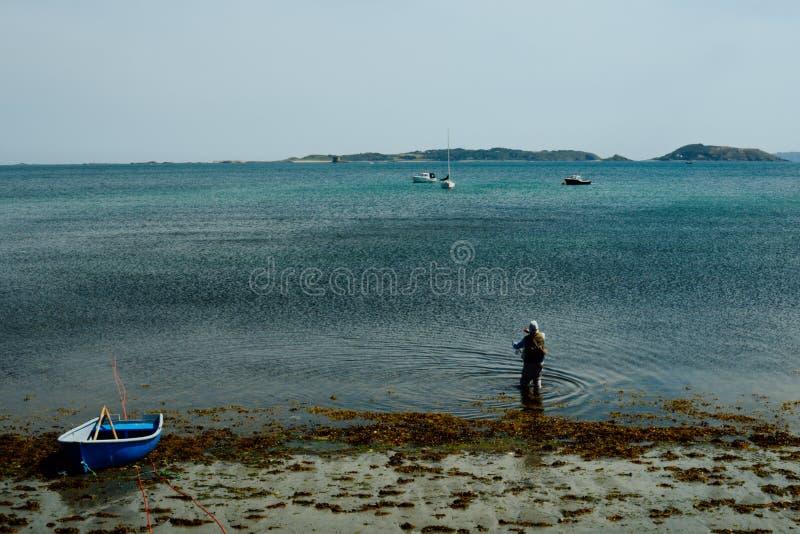 pesca del hombre en la playa de la orilla de mar al lado de un pequeño bote delante de un ancladero imagenes de archivo