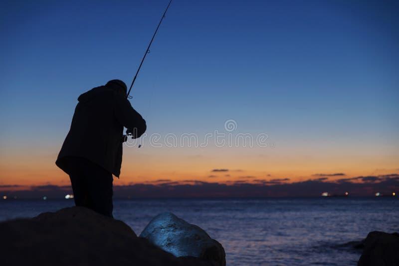 Pesca del hombre en puesta del sol imagen de archivo