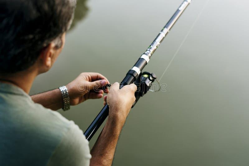 Pesca del hombre por el río foto de archivo