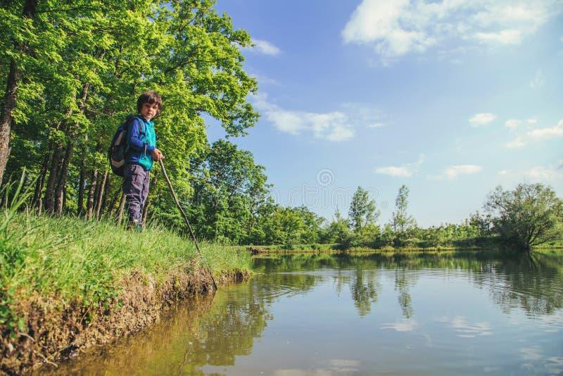 Pesca del juego de ni?os cerca del lago fotografía de archivo libre de regalías