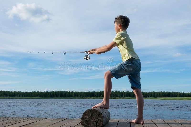 Pesca del muchacho con el giro en el río, fondo del cielo azul imagen de archivo