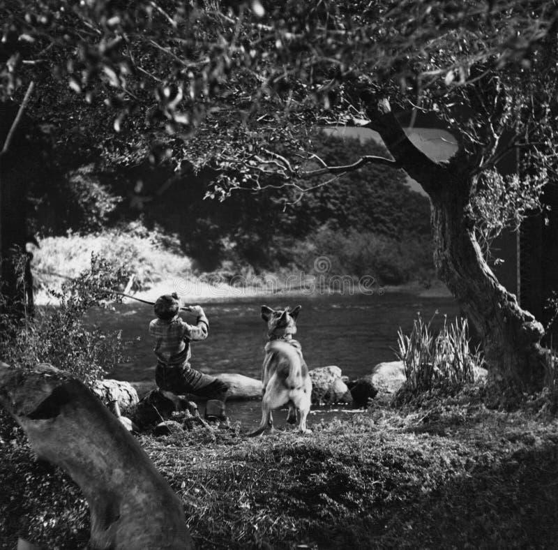 Pesca del muchacho con el perro en el río (todas las personas representadas no son vivas más largo y ningún estado existe Garantí foto de archivo libre de regalías