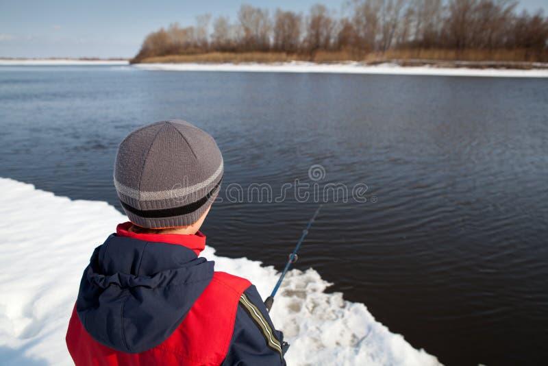 Pesca del muchacho con la barra en el río en invierno imagen de archivo