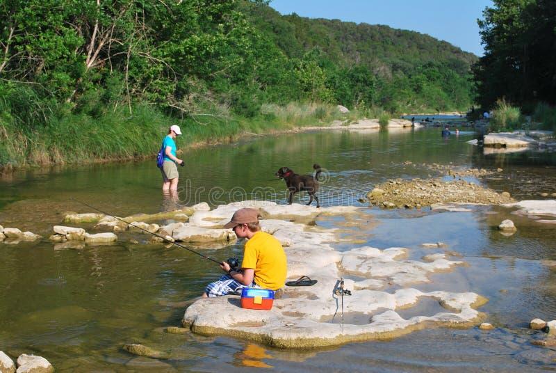 Pesca del muchacho en el río imagenes de archivo