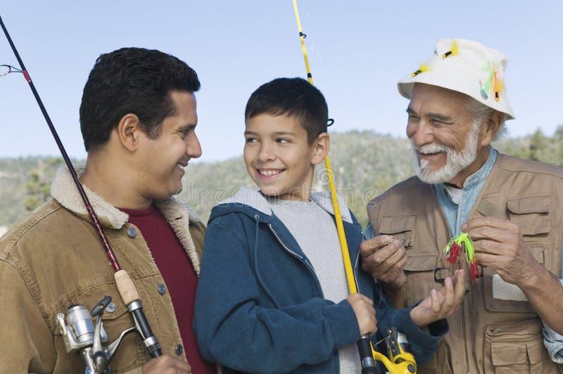 Pesca del ragazzo con il padre ed il nonno immagine stock libera da diritti
