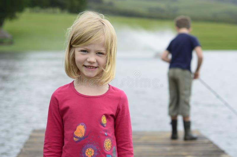 Pesca del ragazzo e della ragazza sul pilastro di legno fotografie stock