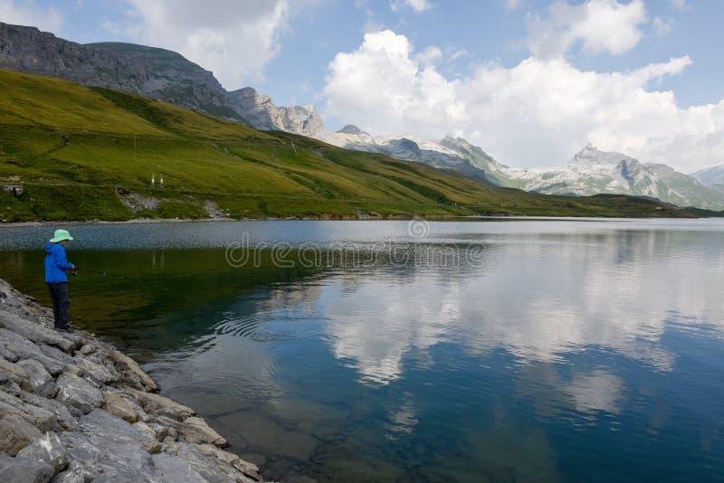 Pesca del ragazzo nel lago Tannensee sulle alpi svizzere immagine stock