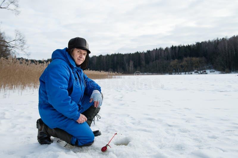 Pesca del viejo hombre en el lago en el día de invierno frío fotografía de archivo libre de regalías