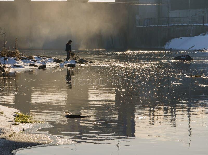 Pesca dell'uomo alla diga fotografia stock