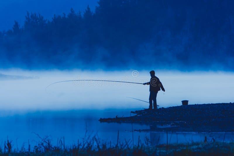Pesca dell'uomo alla riva del fiume fotografia stock libera da diritti