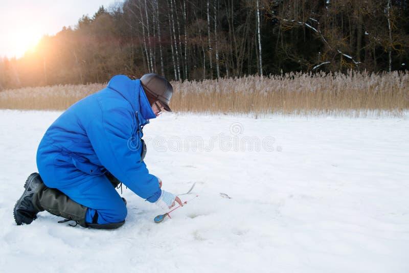 Pesca dell'uomo anziano sul lago al giorno di inverno freddo immagine stock libera da diritti