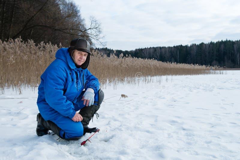 Pesca dell'uomo anziano sul lago al giorno di inverno freddo immagini stock libere da diritti