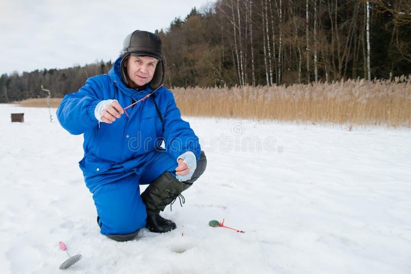 Pesca dell'uomo anziano sul lago al giorno di inverno freddo immagini stock