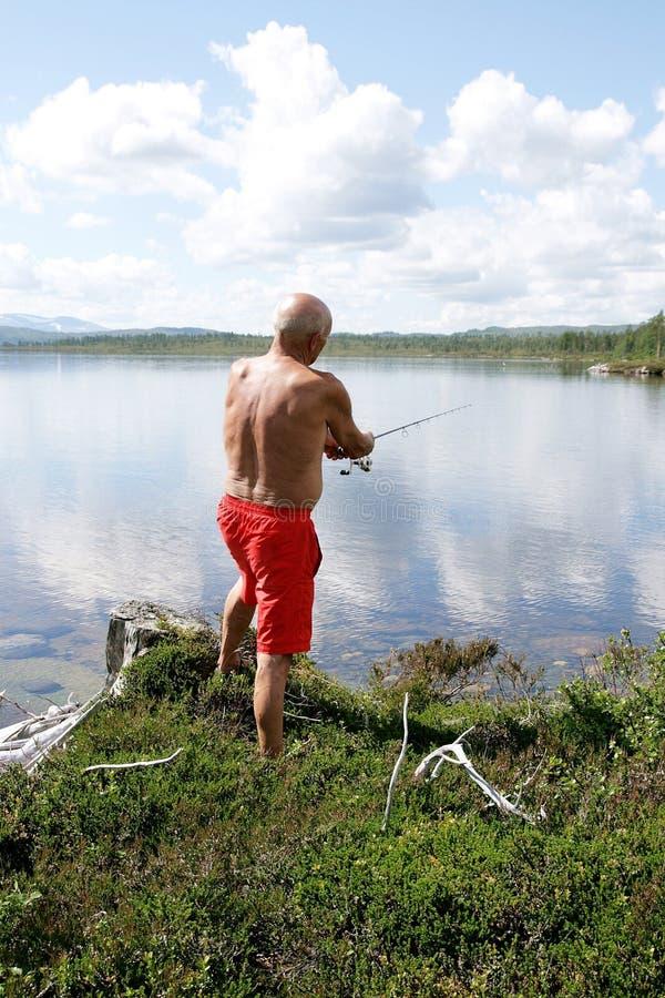 Pesca dell'uomo da un lago immagine stock