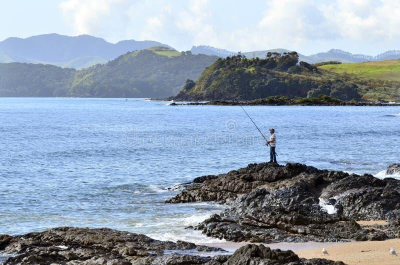 Pesca dell'uomo da una roccia immagini stock libere da diritti