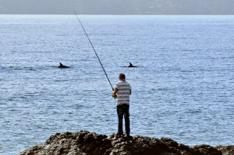 Pesca dell'uomo da una roccia fotografia stock