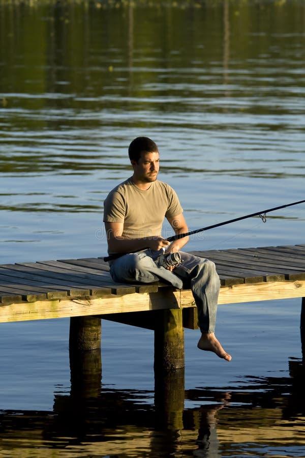 Pesca dell'uomo su un bacino immagine stock