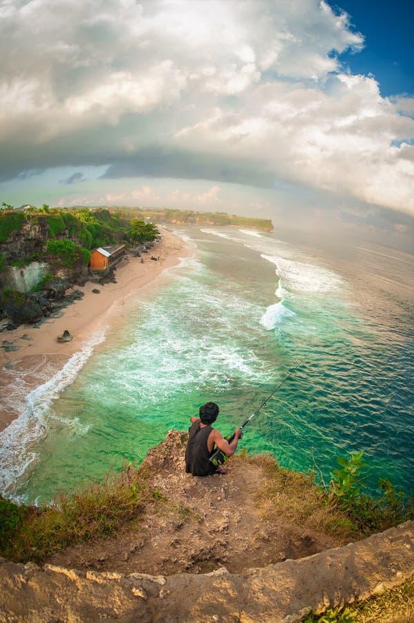 Pesca dell'uomo sul bordo della scogliera sulla costa indiana fotografie stock libere da diritti
