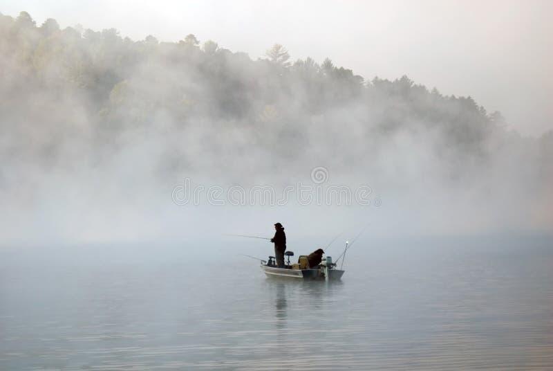 Pesca della barca nella nebbia immagini stock