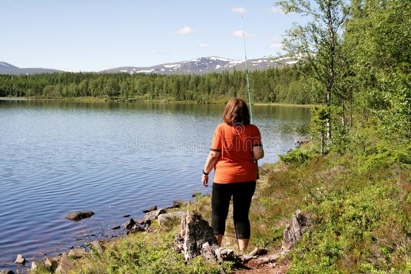 Pesca della donna da un lago immagine stock