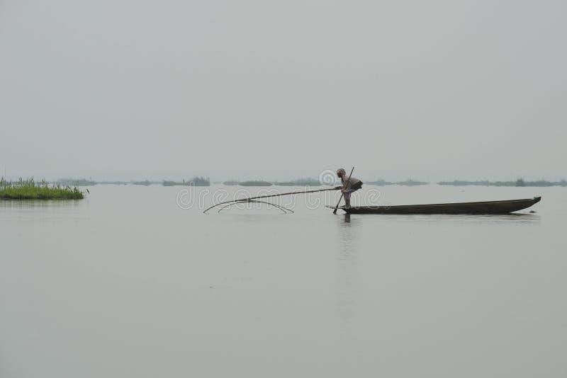 Pesca della donna nel lago con rete immagini stock