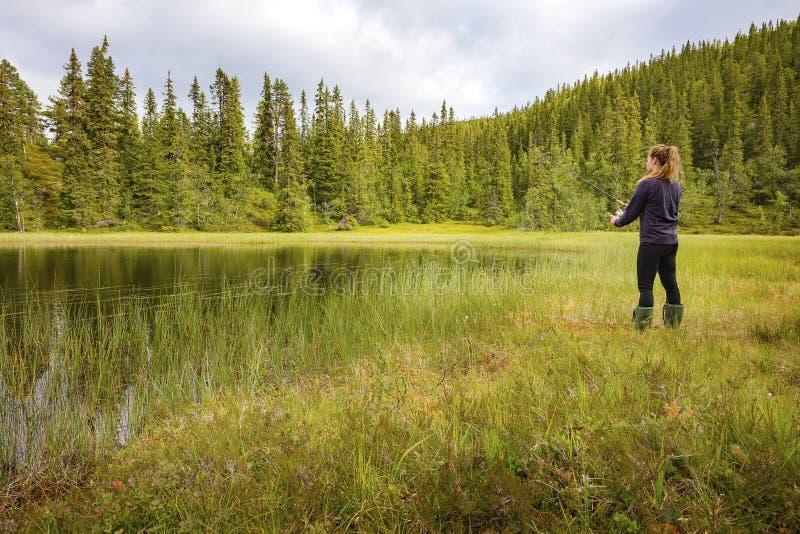 Pesca della donna nell'insenatura dell'acqua dolce nella foresta fotografia stock