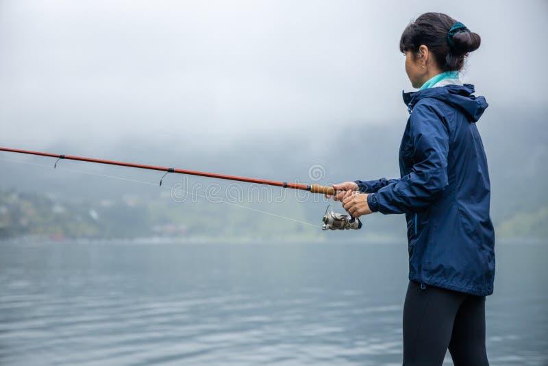Pesca della donna sulla canna da pesca che fila in Norvegia fotografia stock libera da diritti