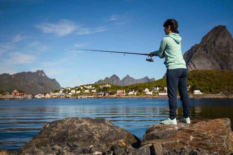 Pesca della donna sulla canna da pesca che fila in Norvegia immagine stock