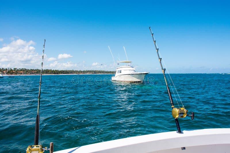 Pesca della pesca a traina filando su una barca bianca nel mar dei Caraibi con acqua blu immagini stock