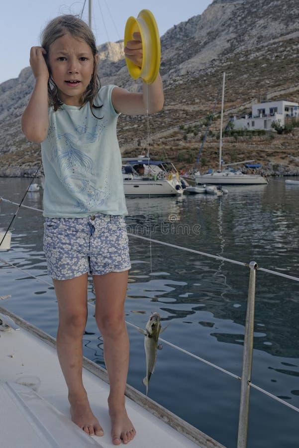 Pesca della ragazza da una barca fotografia stock libera da diritti