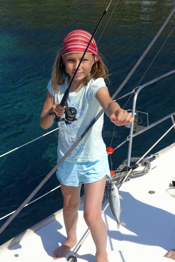 Pesca della ragazza su un yacht di navigazione fotografia stock