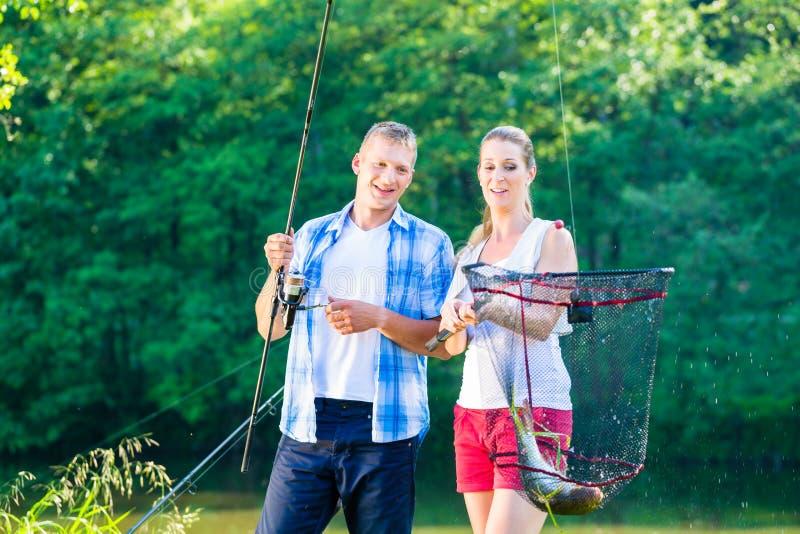 Pesca desportiva dos pares que vangloria-se com os peixes travados fotografia de stock royalty free