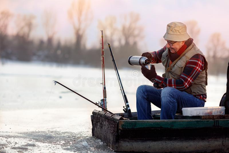 Pesca di inverno Pescatore che si siede sul tè congelato della bevanda e del lago fotografie stock libere da diritti