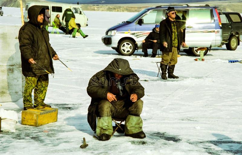 Pesca di inverno sul ghiaccio di Baikal I pescatori sono impegnati nella pesca dell'inverno fotografia stock libera da diritti