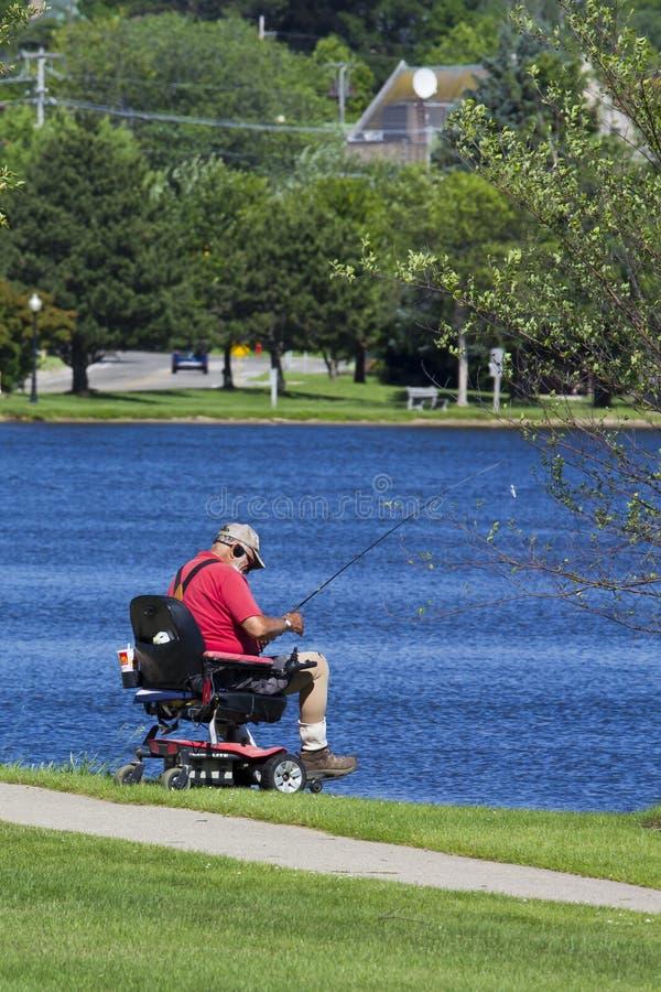 Pesca discapacitada del hombre en un lago foto de archivo libre de regalías