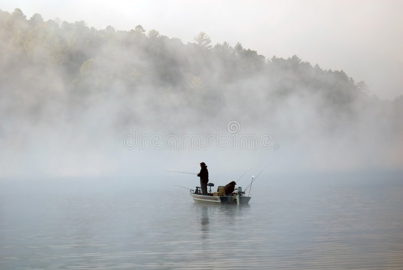 Pesca do barco na névoa imagens de stock
