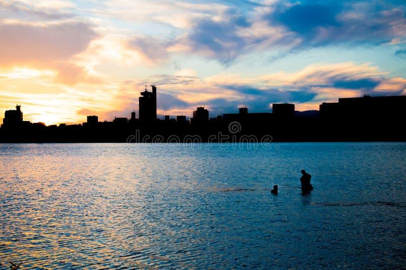 Pesca do homem de Fisher em um rio no por do sol foto de stock