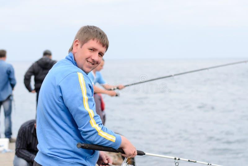 Pesca do homem de um molhe com amigos imagem de stock royalty free